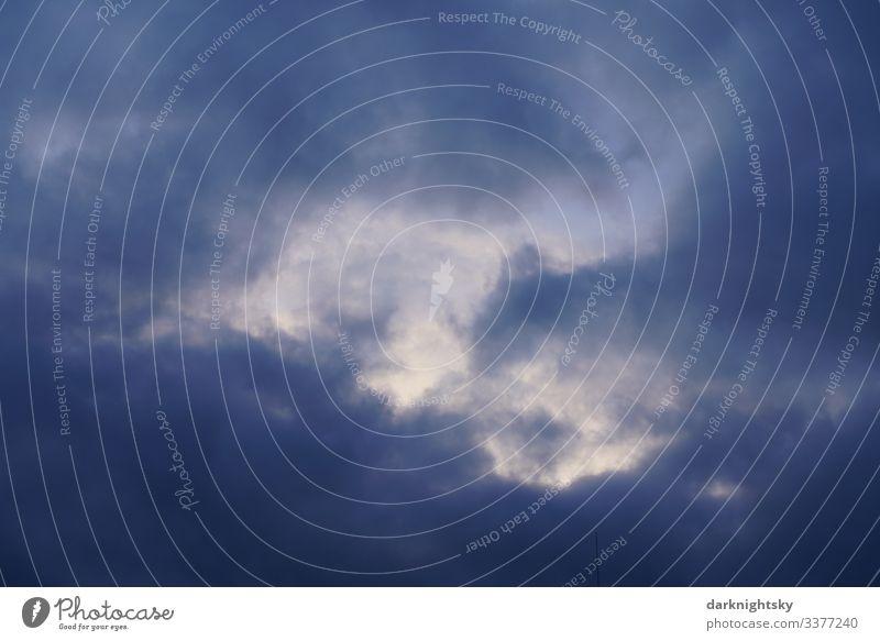 Dunkel blaue Regen Wolken mit Durchblick in die höhere Atmosphäre zur Dämmerung. Eher düstere Stimmung mit einem Lichtblick. Luftraum Meteorologie Pilot Umwelt