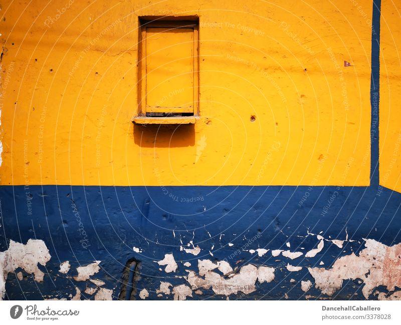 blaue gelbe Wand mit einem geschlossenem Fenster Mauer alt Fassade Architektur trist Gebäude kaputt abblättern geometrisch Design Verfall Vergangenheit