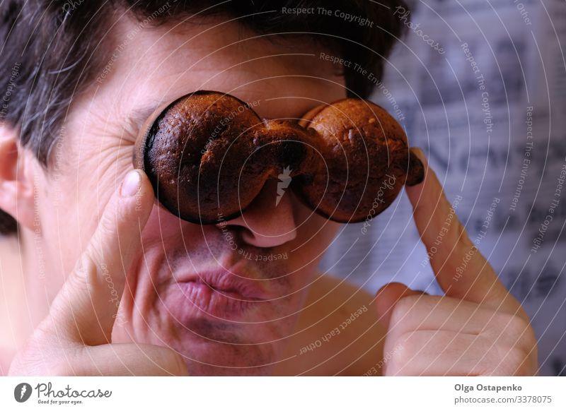 Lustiger glücklicher Mann, der durch das Fernglas zweier Muffins schaut Glück lustig Blick Cupcake Lächeln Zukunft Abenteurer Erfolg Abenteuer 18-30 Jahre