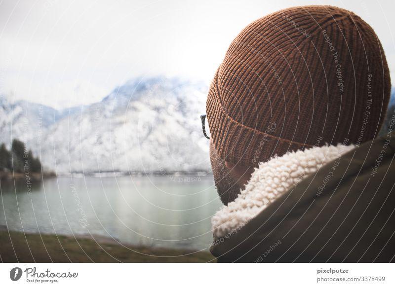 Mann mit Mütze sieht auf Bergsee Alpen Bayern Berge Brille Natur Outdoor See Weite Winter wandern