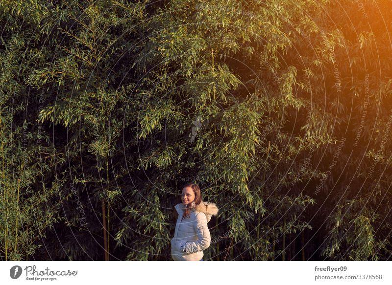 Junge Frau vor einer Bambusplantage jung Schonung Blätter grün Gras Natur Pflanzen Japanisch Blatt Kultur Garten tropisch Hintergrund Zen Frische Baum Asien
