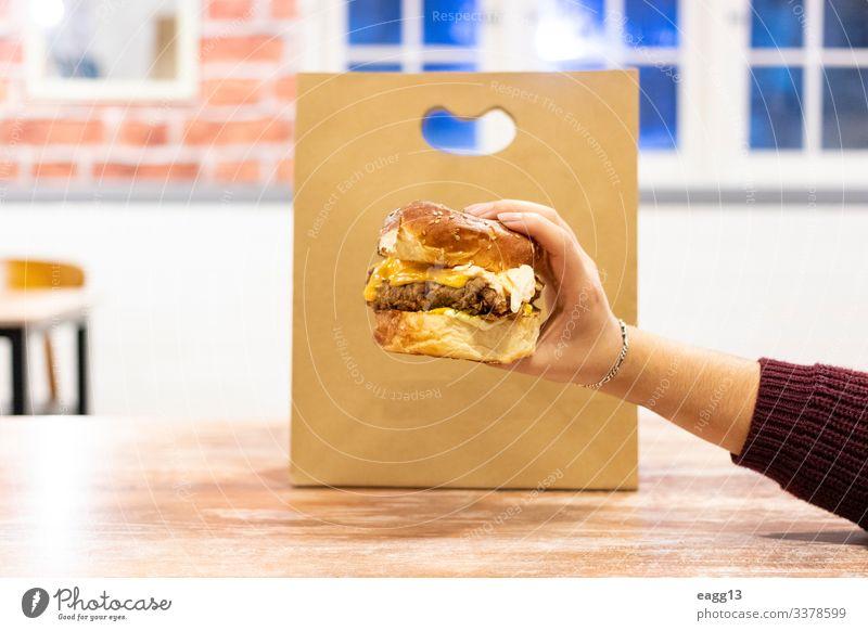 Cheeseburger bereit zur Auslieferung Lebensmittel Fleisch Käse Frühstück Mittagessen Abendessen Fastfood Lifestyle Küche Restaurant Gastronomie Mensch feminin