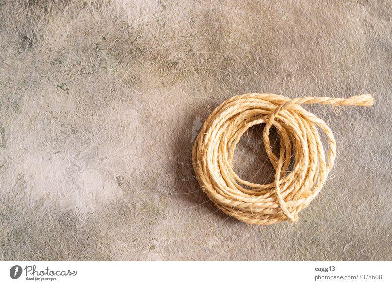 Blick auf eine Seilrolle auf goldenem Hintergrund Dekoration & Verzierung Werkzeug Locken Kugel alt einfach Idee abbaubar Garnspulen Borte geflochten Kabel