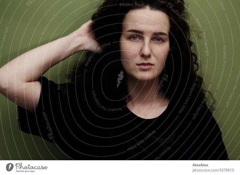 Portrait einer jungen Frau vor grüner Wand elegant Stil schön Leben Wohnung Raum Junge Frau Jugendliche Gesicht 18-30 Jahre Erwachsene T-Shirt brünett