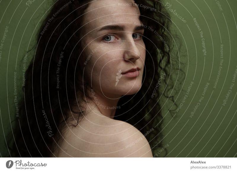 Portrait einer jungen Frau vor grüner Wand Lifestyle Stil schön Wohnung Junge Frau Jugendliche 18-30 Jahre Erwachsene brünett langhaarig Locken Blick warten