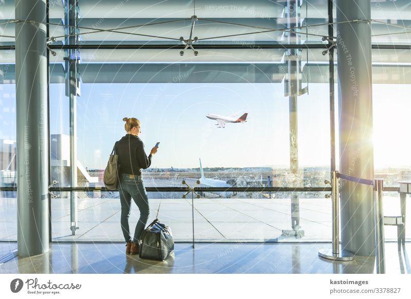 Junge lässige weibliche Reisende am Flughafen, hält Smartphone-Gerät, Blick durch die Flughafen-Gate-Fenster auf Flugzeuge auf dem Flughafen Start-und Landebahn.