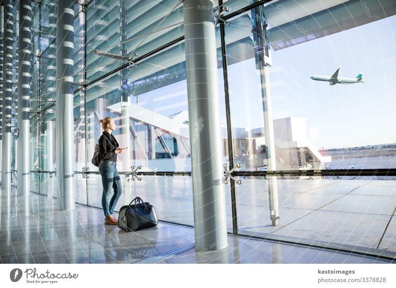 Junge Frau wartet am Flughafen und schaut durch das Fenster. Ferien & Urlaub & Reisen Tourismus Abenteuer Business Telefon Handy PDA Technik & Technologie