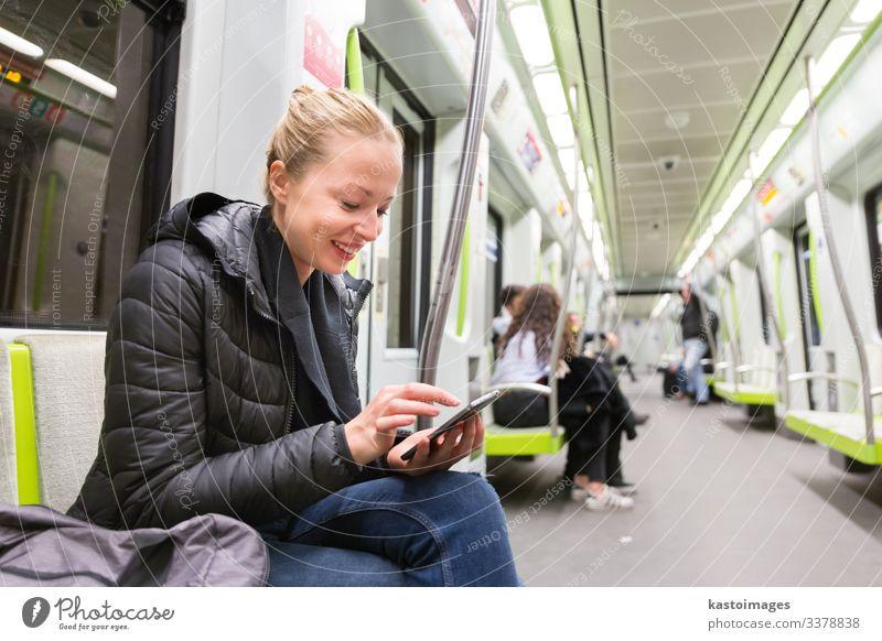 Ein junges Mädchen liest in der U-Bahn vom Bildschirm eines Mobiltelefons. Lifestyle Ferien & Urlaub & Reisen Ausflug Dekoration & Verzierung Business Telefon