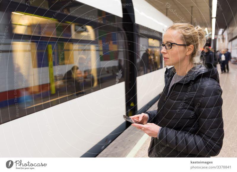 Frau mit einem Handy wartet auf die U-Bahn. Lifestyle Ferien & Urlaub & Reisen Ausflug Dekoration & Verzierung Telefon PDA Mensch Erwachsene Verkehr Eisenbahn