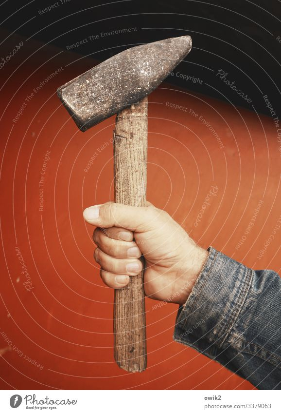 Arbeiterdenkmal Arme Hand Finger Daumen Hammer Hammerkopf Griff Holz Metall alt kaputt festhalten Neigung Schaden Zahn der Zeit Farbfoto Außenaufnahme