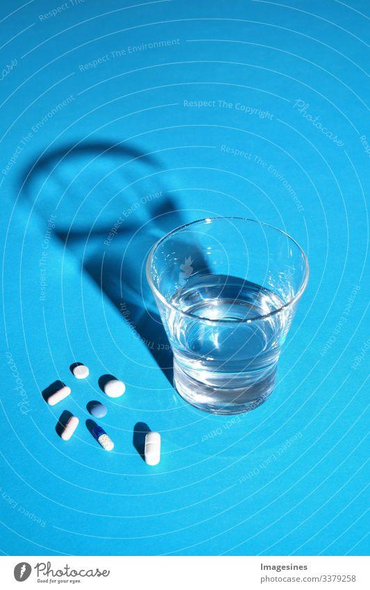 Glas Wasser und Vitamine, Pillen und Tabletten auf blauem Hintergrund mit Text Freiraum Antibiotikum Aspirin Kapsel Nahaufnahme Konzept Kopierraum Heilung