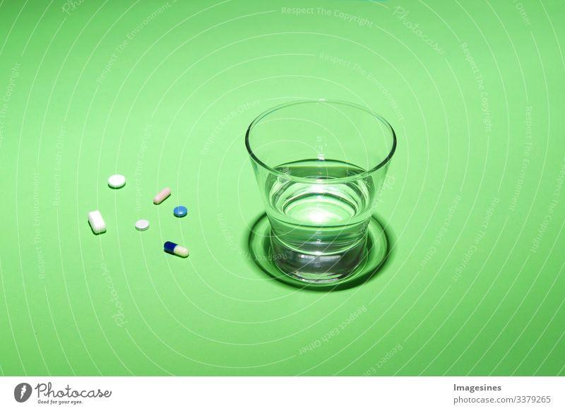 Glas Wasser und Vitamine, Pillen und Tabletten auf grünem Hintergrund mit Text Freiraum grüner Hintergrund Antibiotikum Aspirin Kapsel Nahaufnahme Konzept