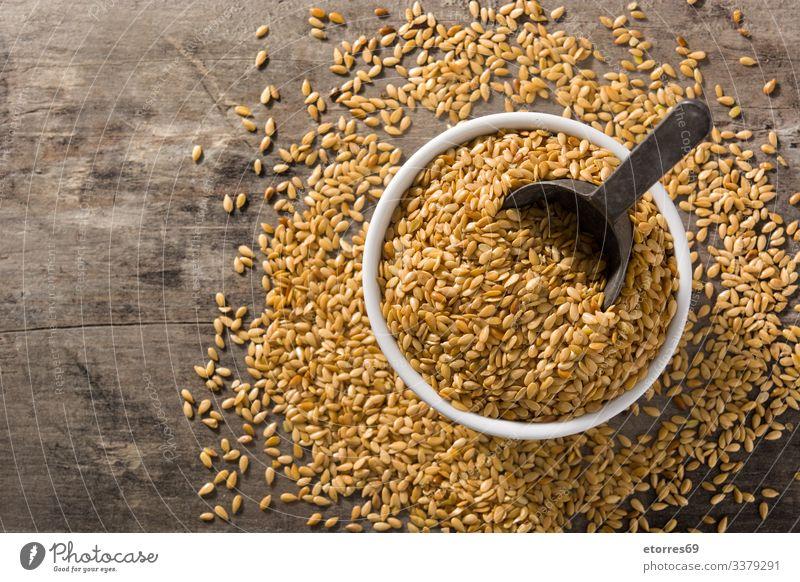 Goldene Leinsamen in Schale auf Holztisch. Ansicht von oben. Raum kopieren Lebensmittel Müsli trocknen Ackerbau Korn Gesundheit organisch Schalen & Schüsseln