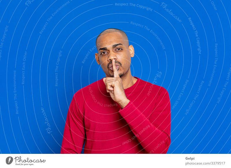Afrikanischer Typ mit rotem Trikot ruhig Mensch Mann Erwachsene Lippen Finger Afro-Look Lächeln blau schwarz weiß Stille Orden zeigen stumm schalten Menschen
