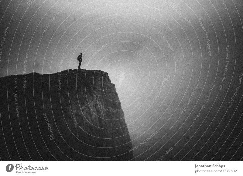 Junge Frau steht an einer Klippe im Nebel abstrakt schwarz minimalistisch Schwarzweißfoto Vor dunklem Hintergrund bedrohlich gefährlich Risiko dunkel dunkelgrau
