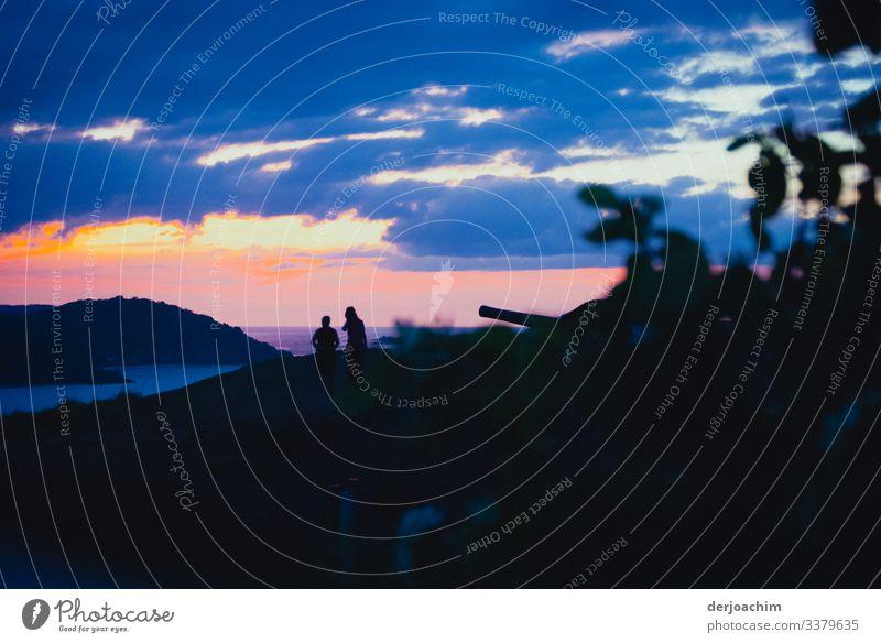 Zwei Frauen unterhalten sich beim Sonnenuntergang auf einer Insel. Dunkler Vordergrund mit Kanone. Blaue Wolken und mit Blick auf eine Nachbar Insel. Farbfoto