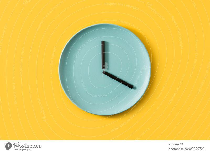 Uhr mit Platte und Strohhalmen auf gelbem Hintergrund Teller gemacht Lebensmittel leer Zeit Konzept Küche Küchengeräte blau schwarz essen Zeit zum Essen Farbe