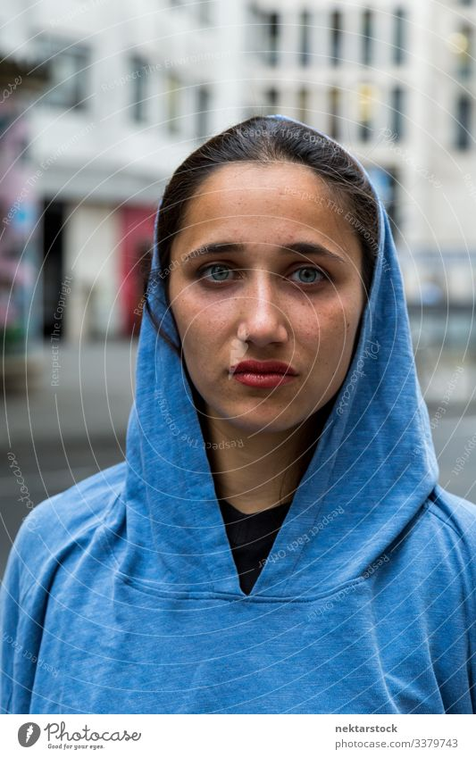 Junge Frau aus dem Nahen Osten trägt anständigen blauen Kapuzenpullover junger Erwachsener Kopfdeckel Gesicht gebräunter Teint Porträt Jugendkultur Tag urban