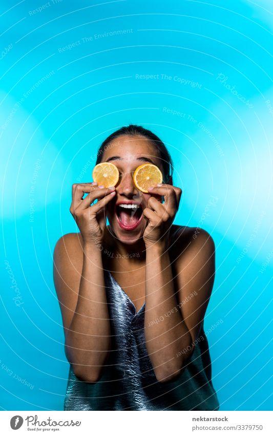 Junge Frau hält Zitronenscheiben über die Augen und lächelt breit Scheibe Mädchen Überfall Konzept Minimalismus Zitrusfrüchte Frucht frisch Frische Lächeln
