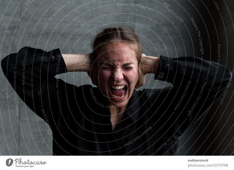Junge Frau schreit unter Höllenqualen und hält sich die Hände vor die Ohren Hände auf dem Kopf schreien Mädchen Qual junger Erwachsener Terror Entsetzen