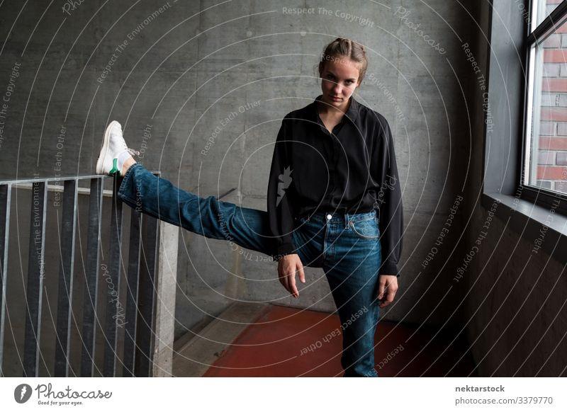 Junge Frau mit Bein am Treppengeländer schaut in die Kamera Geländer Bein angehoben Mädchen Dehnung junger Erwachsener Jugendkultur Tag weibliche Schönheit