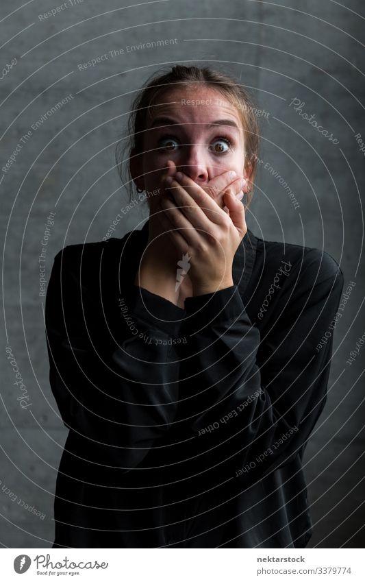 Junge kaukasische Frau mit Händen auf dem Mund und verängstigtem Gesichtsausdruck Hände auf Mund schreien Mädchen junger Erwachsener Terror Entsetzen Stille