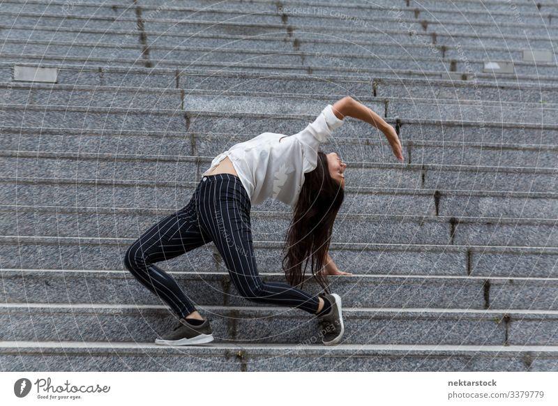 Junge Frau im Rückstand steht auf Marmortreppen Handstand Tanzen Mädchen junger Erwachsener Jugendkultur Tag lässig Treppenhaus Freitreppe im Freien 1 Mensch