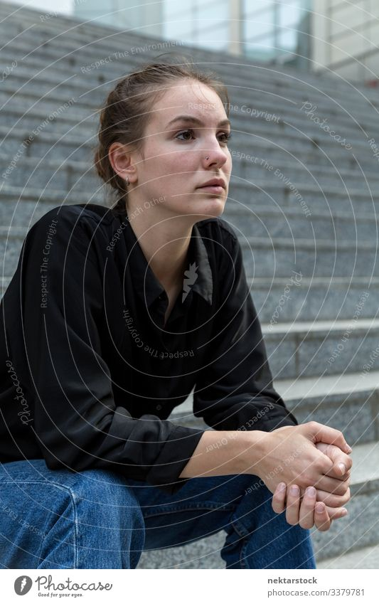 Seitenansicht Porträt einer jungen kaukasischen Frau, die auf einer Treppe im Freien sitzt Sitzen Mädchen Freitreppe Murmel Stein Wegsehen ernst stark