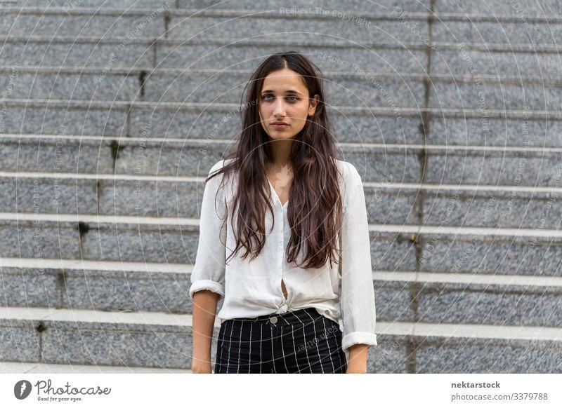 Junge Schönheit aus dem Nahen Osten blickt mit neutralem Gesichtsausdruck Frau Mädchen Stehen junger Erwachsener Jugendkultur Tag urban schöne Frau
