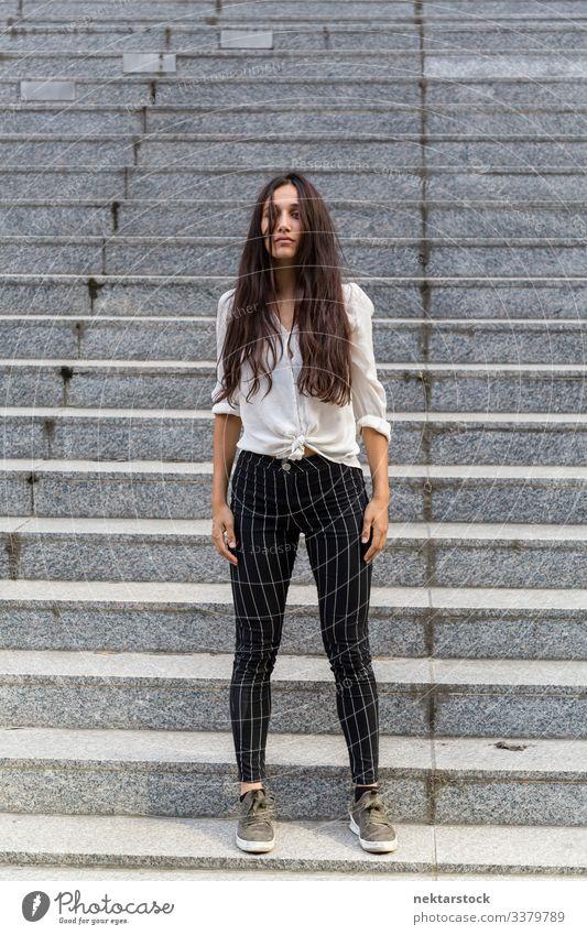 Natürliche Schönheit auf steinernen Stufen stehend Frau Mädchen Stehen neutral Gesichtsausdruck junger Erwachsener Jugendkultur Tag urban schöne Frau