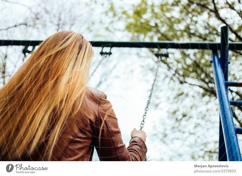 Junge Frau auf einer Schaukel auf einem Spielplatz Lifestyle Freude Freiheit Mensch feminin Jugendliche Erwachsene Leben 1 30-45 Jahre genießen schaukeln