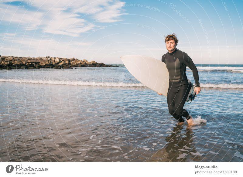 Surfer, der mit einem Surfbrett unter dem Arm das Wasser verlässt. Mann Brandung Sport Surfen MEER Meer im Freien sportlich malerisch Küstenlinie Wellen