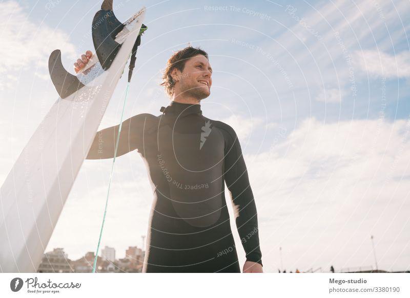 Surfer, der mit einem Surfbrett am Strand steht. Mann Brandung Wasser Sport Surfen MEER Meer im Freien sportlich Küstenlinie Wellen Hintergrund Abenteuer