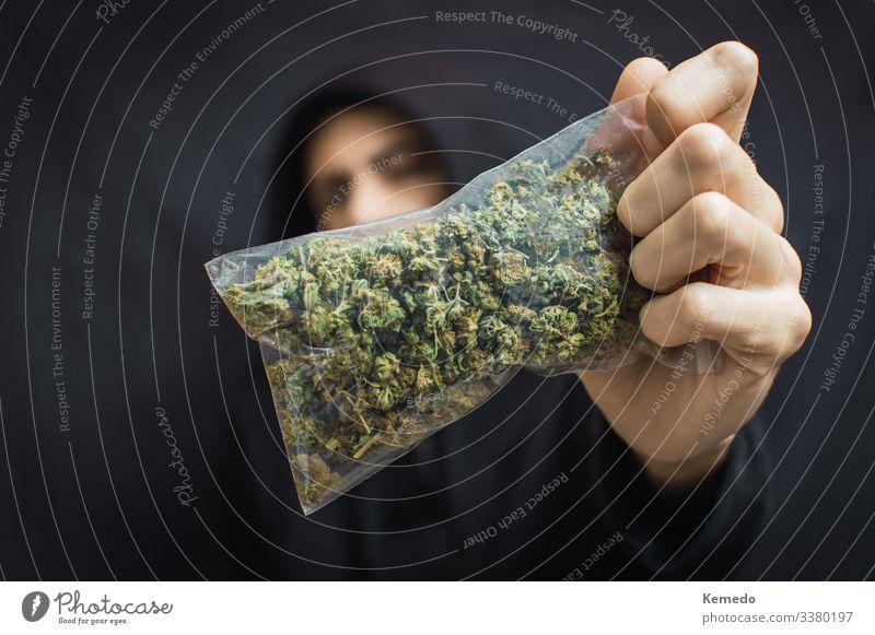 Ein Mann mit Kapuze hält einen großen Sack Unkraut vor seinem Kopf auf schwarzem Hintergrund. Drogenhandelskonzept, Marihuana kaufen oder verkaufen.