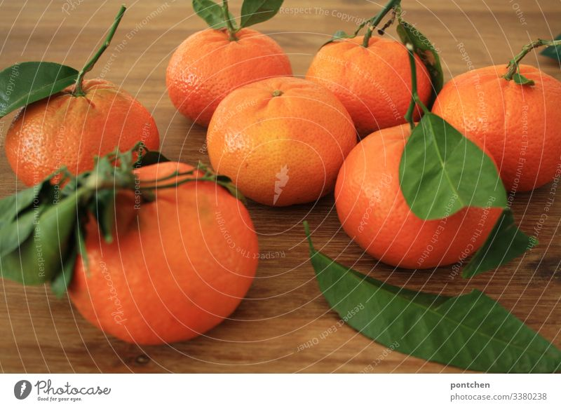 Sieben Mandarinen mit grünen Blättern liegen auf einem Holztisch Lebensmittel Frucht Ernährung Bioprodukte Diät sauer orange Blatt Tisch Gesundheit