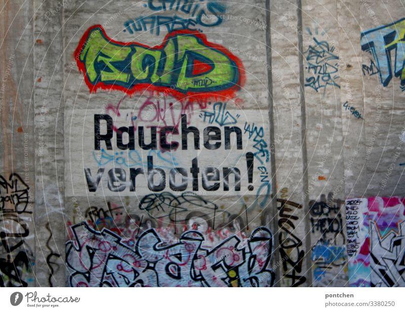 """Aufschrift """"Rauchen verboten"""" auf Gebäudewand mit Graffiti rauchen aufschrift gebäude bunt außenaufnahme wörter hinweis Gefahr Zigarette Verbote Gesundheit"""