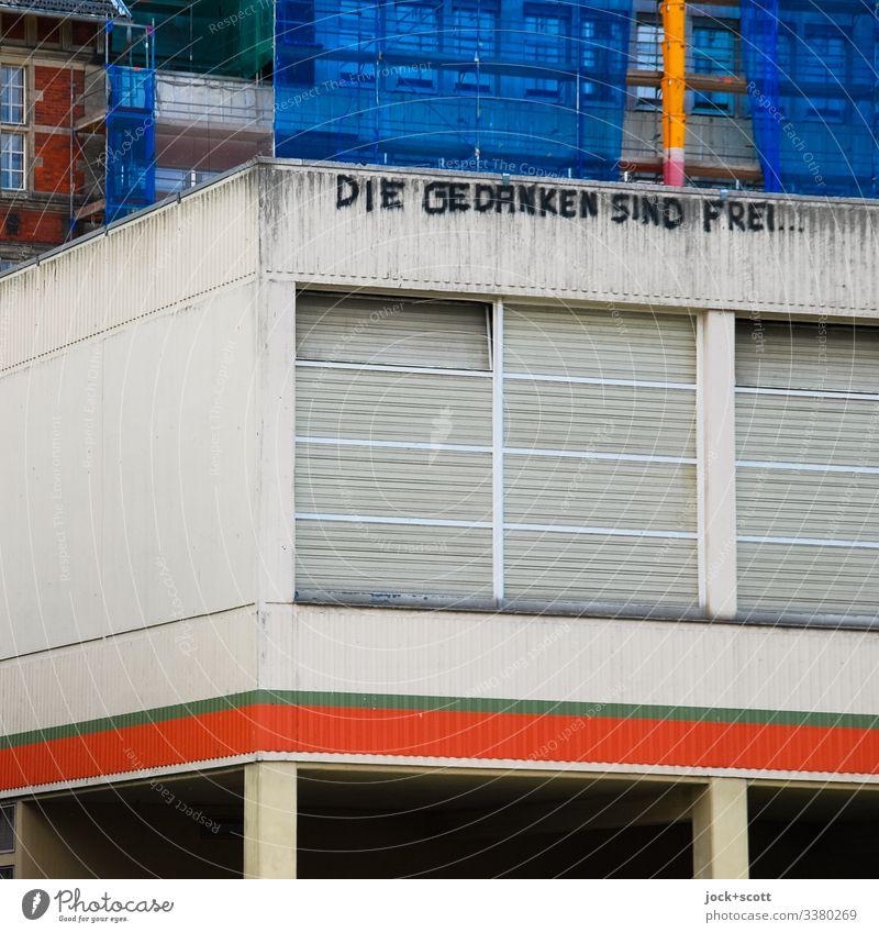 Die Gedanken sind frei an einem Gebäude aus Beton Typo Architektur Außenaufnahme Fassade Wand Farbfoto grau Tag Gedeckte Farben Streetart Menschenleer