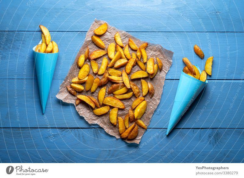 Gemüse Abendessen Fastfood lecker gold obere Ansicht amerikanische Pommes frites Ofenkartoffel gebackene Keile blaue Kegel blauer Tisch knusprige Pommes frites