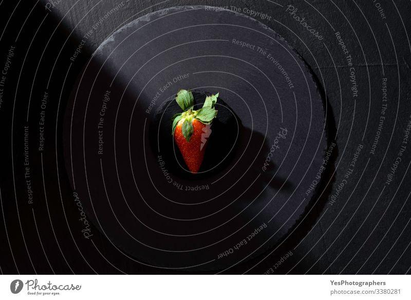 Einzelne Erdbeere auf schwarzer Platte in grellem Licht. Frucht Dessert Bioprodukte Gesunde Ernährung frisch obere Ansicht ganz schwarz schwarzer Hintergrund