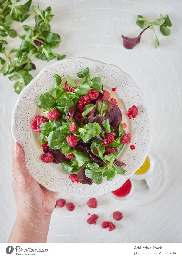Person hält Teller mit Himbeer-Spinat-Salat Himbeeren Salatbeilage Koch frisch Beeren organisch süß lecker geschmackvoll natürlich grün Vegetarier Gesundheit