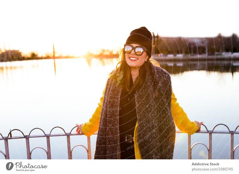 Charmante Frau in Freizeitkleidung am Ufer des Sees Natur Stil heiter Park Freiheit genießen Herbst Glück Saison kalt Teich reisen Wasser Sonnenuntergang