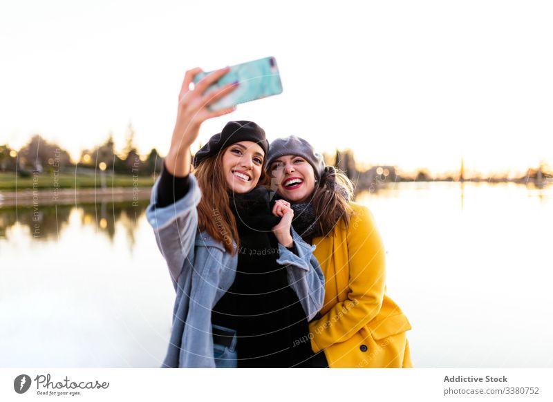Gelegenheitsfrauen beim Selbermachen mit dem Smartphone am sonnigen See Frauen Freund Selfie reisen Natur Herbst Freundin Spaß Park Sonnenuntergang Zusammensein