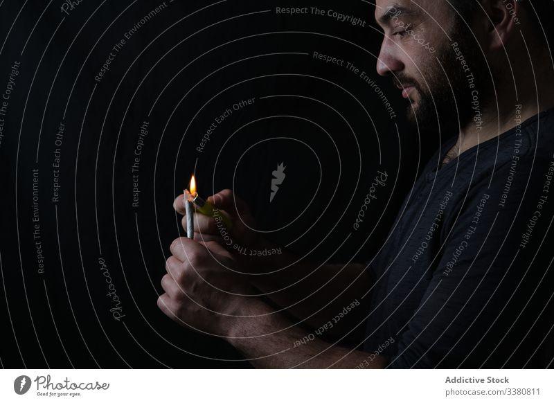 Erwachsener Mann raucht Cannabis-Joint Rauch Gelenk Raucherin stumpf Feuerzeug Licht Marihuana Unkraut Medikament männlich ganja medizinisch hoch Erholung Dope
