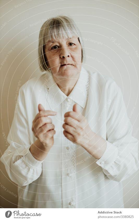 Alte Frau gestikuliert im Studio alt gestikulieren älter zeigen Hände hoch Senior heimwärts Rentnerin ernst natürlich Bluse Zeitgenosse Zeichen Veranstaltung