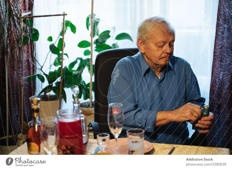 Älterer Mann öffnet Champagnerflasche während der Weihnachtsfeier zu Hause offen heimwärts feiern lässig trinken Tisch Senior Flasche Winter gealtert männlich