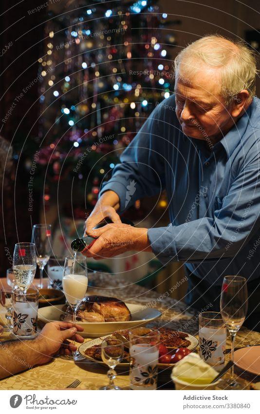Alter Mann schenkt beim Weihnachtsessen zu Hause Champagner in Gläser ein Weihnachten feiern heimwärts Flasche Glas gealtert Senior lässig trinken Getränk