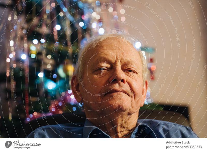 Positiver männlicher Rentner sitzt am Heiligabend zu Hause Mann lässig Senior heimwärts Weihnachten Windstille sich[Akk] entspannen positiv sitzen wohnlich