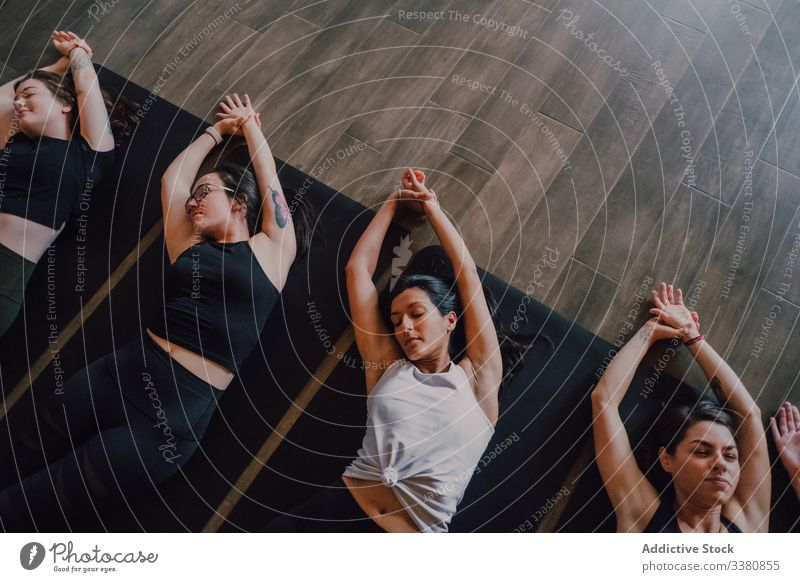 Ruhige Athleten, die zusammen Yoga praktizieren und in einem zeitgenössischen Trainingsraum eine Leichenhaltung einnehmen sich[Akk] entspannen Übung savasana