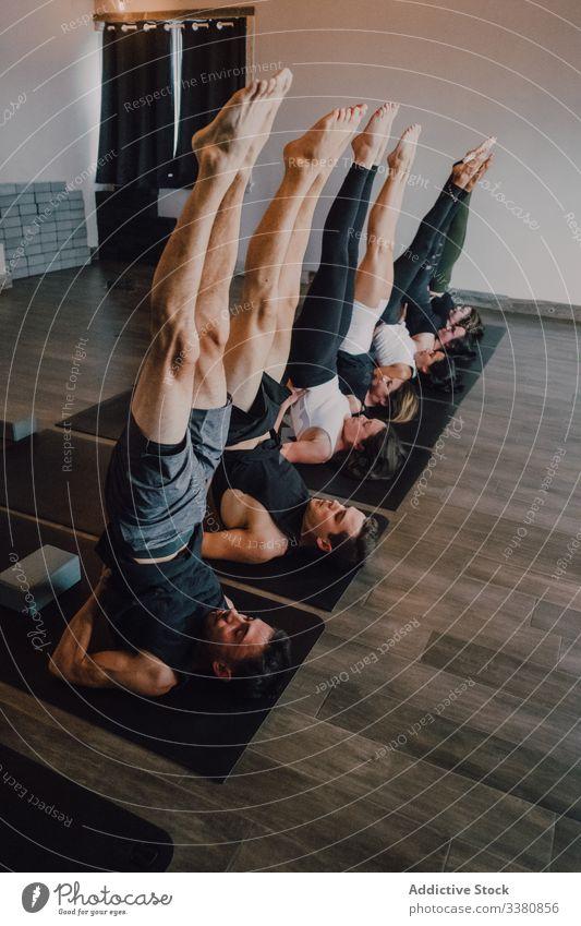 Fokussierte Athleten, die gemeinsam Yoga praktizieren und eine gestützte Schulterstand-Balance-Position im modernen Fitnessstudio einnehmen gymnastisch