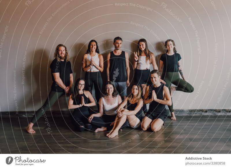 Gruppe fröhlicher Athleten in verschiedenen Yoga-Posen im zeitgenössischen Trainingsraum Klasse Gleichgewicht üben Glück Atelier Namaste Club Dehnung Menschen